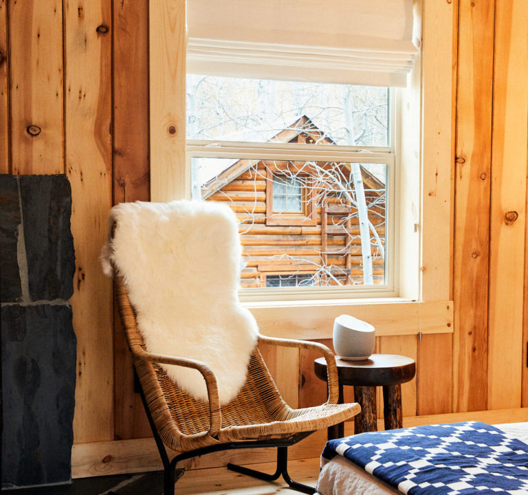 Guest chair with fur throw and window looking out at another cabin