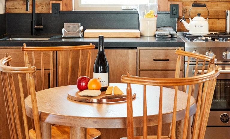 Dining table in cabin with cheese palter and wine