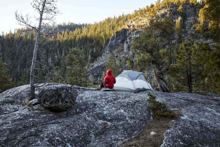 Camp site with guest sitting outside tent looking at nature