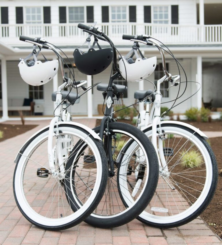Three bikes parked outside hotel with helmets hanging on the handle