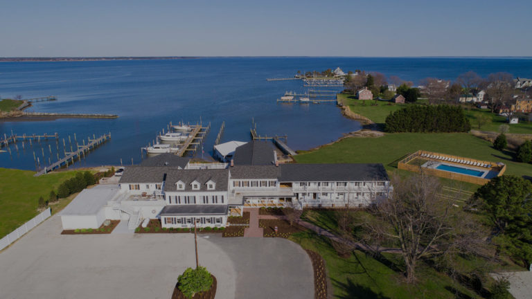 Drone shot of hotel, bay, and dock