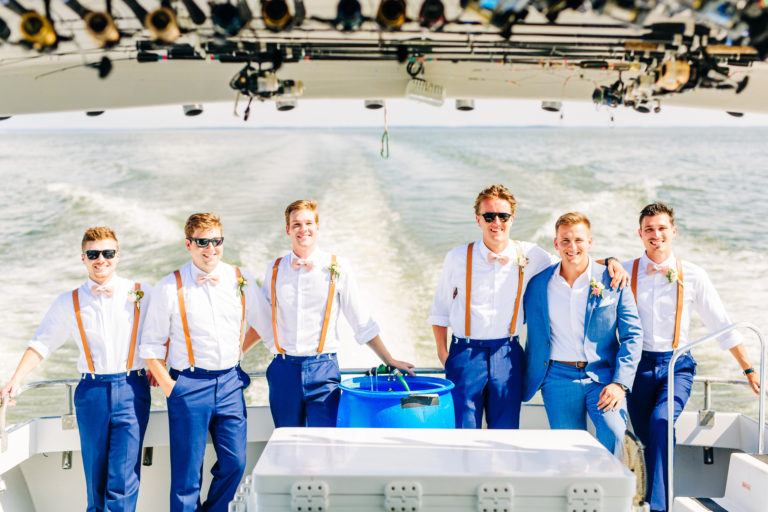 A groom and his groomsman posing on fishing boat