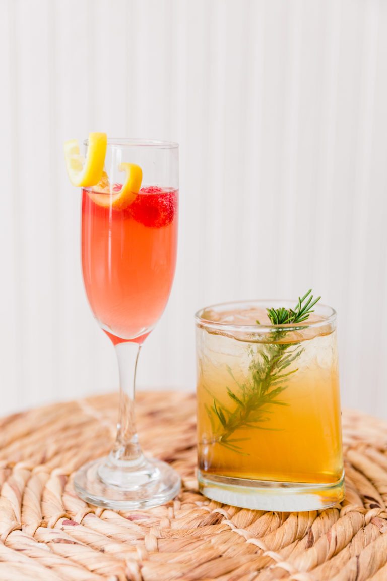 Two cocktails, one with raspberry and champagne and the other with a liquor and sage