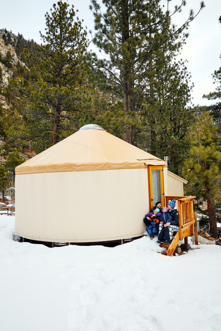 Yurt in winter with family sitting outside