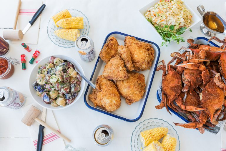 Table with a display of food such as fried chicken, crab, and potato salad